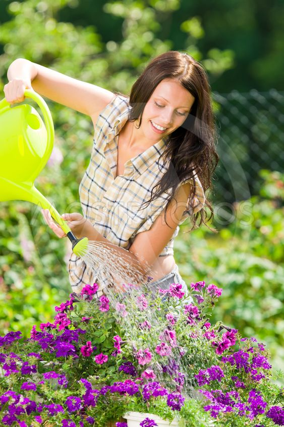 Gardening smiling woman watering can violet flower