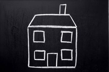 A child?s chalk drawing of a house on a blackboard.