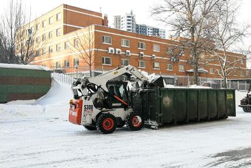 Small front-end loaders clear snow from the street and...