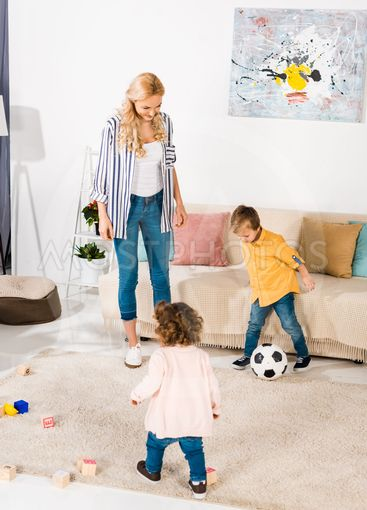 cheerful mother and cute little children playing with...