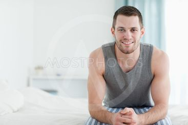Smiling man sitting on his bed