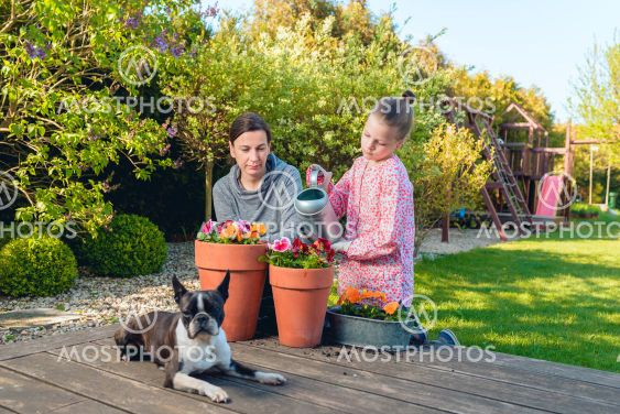 Mother and daughter planting flowers in pots in the...