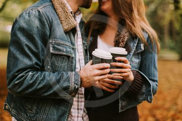 Romantic couple with coffee walking outdoors in the...