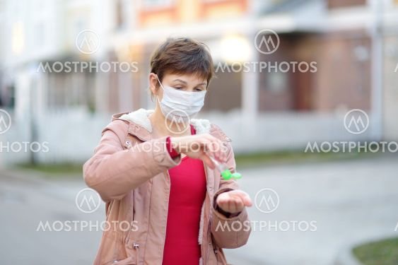 Mature woman wearing disposable medical face mask makes...