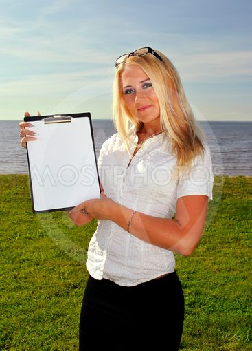 Girl holding a blank paper against the sea