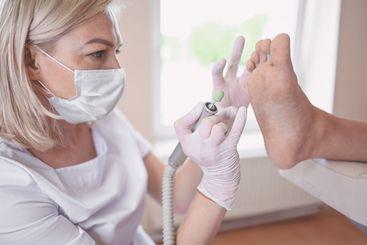 Podiatrist using grinding equipment and making procedure...