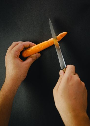 Two hands cutting a carrot with a long knife