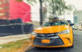 Yellow cab speeding up in New York street