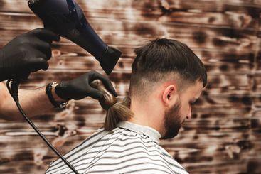 Haircut head in barbershop. Barber cuts the hair on the...
