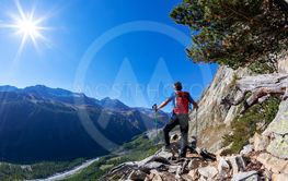 Hiker takes a rest observing a mountain panorama. Mont...