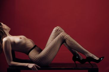 Woman with nude breasts and legs in fishnet tights lays