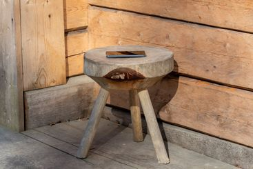 Mobile phone lying on wooden stool
