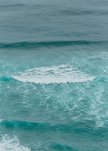 Aerial view of the ocean with the waves and re rocks...