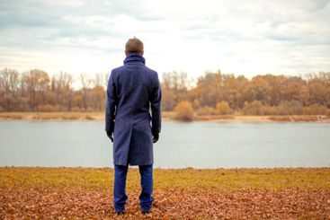 A man stands on the bank of a river on a cold autumn day