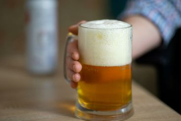 Male hand holding large mug full of cold beer