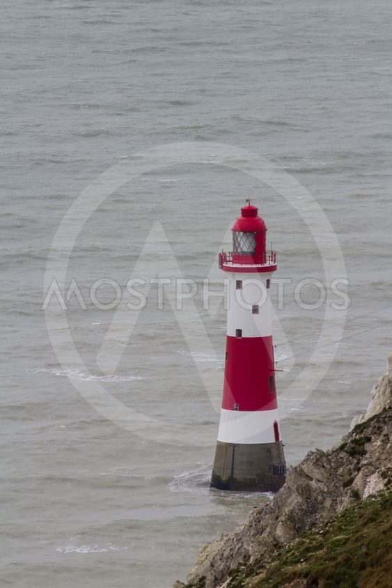 Lighthouse red and white striped on stormy winter day.