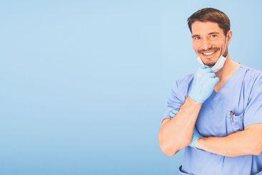 Young smiling handsome dentist doctor in blue medical...