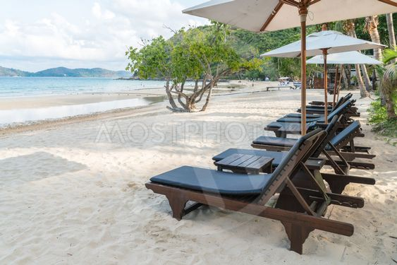 Beautiful beach chairs with umbrella on tropical white...