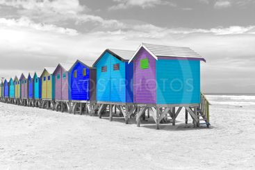 Blue and purple painted beach huts in Cape Town