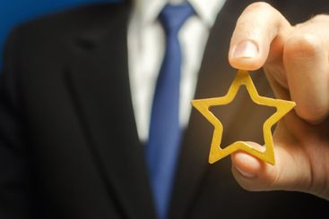 Man holds a golden star in his hand. Symbol of success...