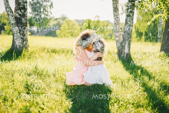 mom hugs her daughter sitting on the grass outdoors on a...