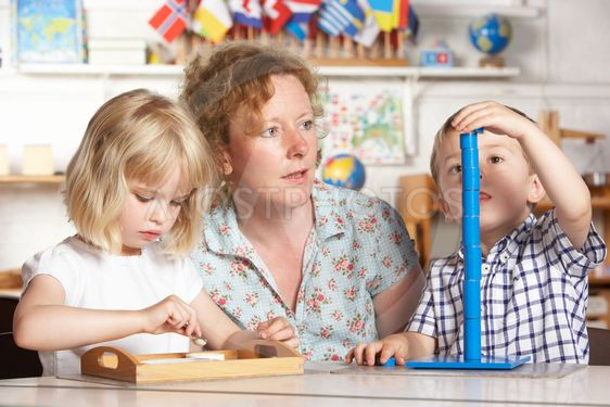 Adult Helping Two Young Children at Montessori/Pre-School