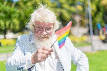 White bearded old man waving the rainbow flag at the...