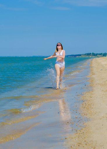 A young girl runs along the sandy sea beach along the...