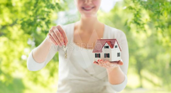 close up of hands holding house model and keys