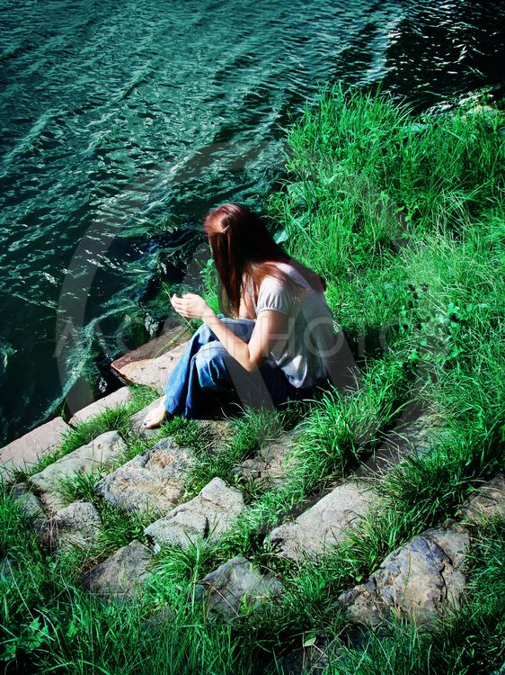 Young woman sitting on the riverbank