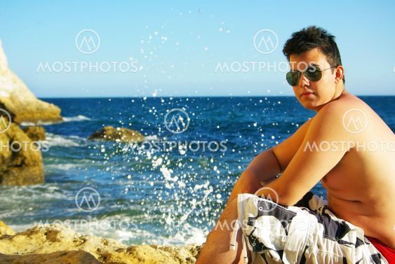 Young man next to the blue sea.