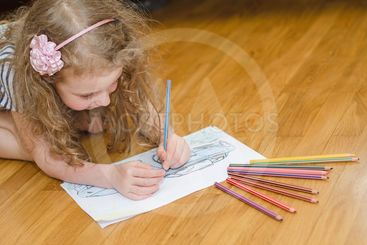 Little girl drawing car with colored pencils.