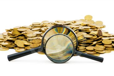 Magnifying glass and coins isolated on white