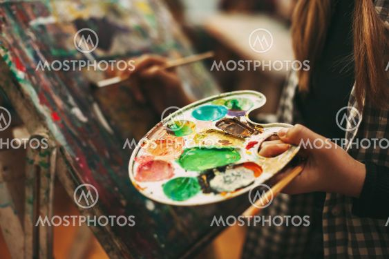 Palette with paints close-up in the hands of a girl, art...