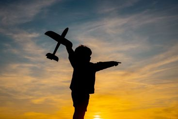 Child playing with toy plane during sunset time in...