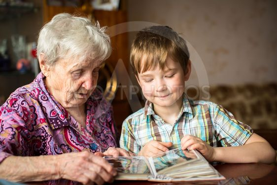 Elderly woman with her little grandson looking album