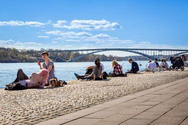 Människor som solar vid vatten i Stockholm.