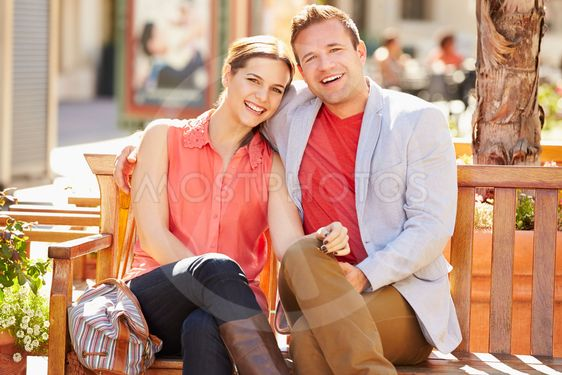 Young Couple Sitting On Seat In Mall Together