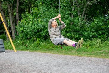 Kvinna åker linbana på lekplats utomhus.
