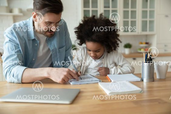 Caucasian stepfather helps with homework little...