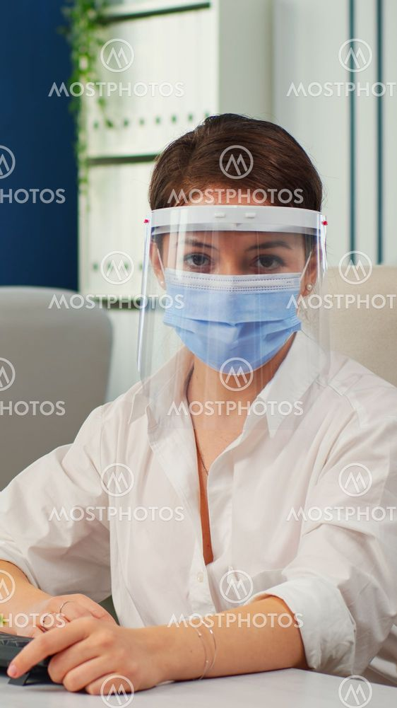 Businesswoman with visor and mask talking in front of...