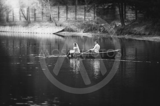 Black and white photo bride and groom riding on boat on...