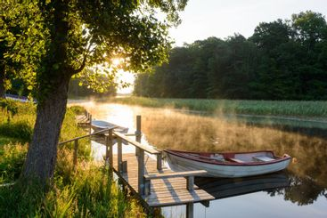 Rowboats moored on a sunlit, misty lake