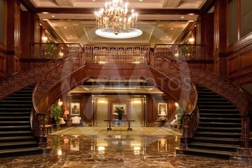 Twin Curved Staircases Under Large Chandelier