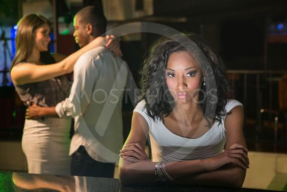 Unhappy woman sitting at bar counter and couple dancing...