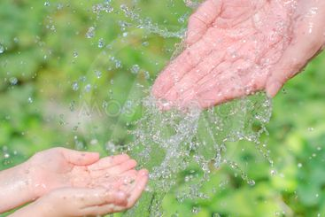 Child's and woman's hands playing with water