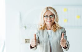 cheerful recruiter in glasses showing thumbs up in office