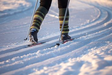 Legs of a skier on nordic skiing track