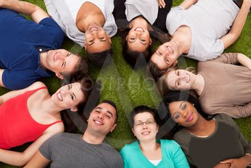 Portrait Of Confident College Students Lying On Grass
