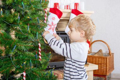 Cute little kid decorating Christmas tree, indoor